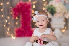 Séance an du bébé 1-2 mignon sur le plancher avec les ballons roses dans la chambre au-dessus du blanc D'isolement Fête d'anniver photographie stock libre de droits