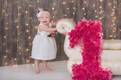 Séance an du bébé 1-2 mignon sur le plancher avec les ballons roses dans la chambre au-dessus du blanc D'isolement Fête d'anniver image libre de droits