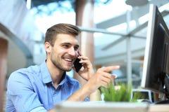 Séance et à l'aide de sourire d'homme d'affaires du téléphone portable dans le bureau image libre de droits