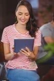 Séance et à l'aide de sourire de femme de la tablette Image libre de droits