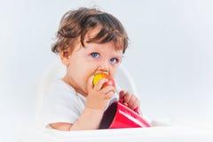 Séance et consommation heureuses de bébé garçon Photographie stock libre de droits