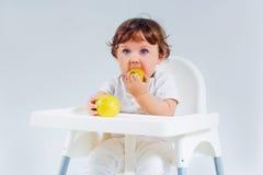 Séance et consommation heureuses de bébé garçon Image stock