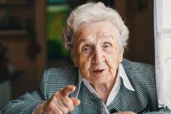 Séance et entretien heureux pluss âgé de femme dans sa maison photographie stock