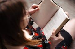 Séance et lecture de fille Image stock