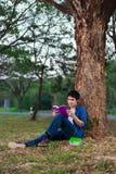 Séance et lecture de jeune homme un livre en parc Photographie stock