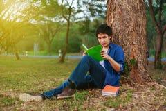 Séance et lecture de jeune homme un livre en parc Photo libre de droits