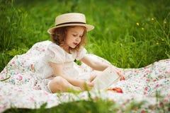 Séance et lecture de petite fille photo stock