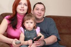 Séance et montre TV de mère, de père et de descendant Image libre de droits