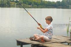 Séance et pêche de garçon d'un dock Photos libres de droits