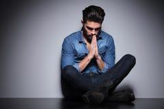 Séance et prière d'homme Photo libre de droits