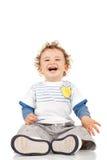 Séance et rire de petit garçon photographie stock libre de droits