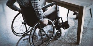 Séance exécutive handicapée sur le fauteuil roulant au bureau image stock