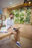 Séance exécutive masculine sur le bureau et l'ordinateur portable d'utilisation Image stock
