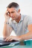 Séance fatiguée d'homme et à l'aide de son ordinateur portable image stock