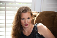 Séance femelle blonde mûre de portrait de plan rapproché sur Sofa Looking Away From Camera Images libres de droits