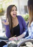 Séance femelle de jeune métis expressif et parler avec la fille Photos stock