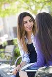 Séance femelle de jeune métis expressif et parler avec la fille Image stock