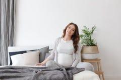 Séance femelle enceinte sur un lit photos libres de droits