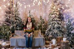Séance femelle heureuse sur un banc ou une oscillation au-dessus des lampes-torches Image libre de droits