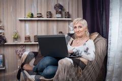 Séance femelle supérieure dans la chambre et l'Internet confortables de lecture rapide avec de la La Photos libres de droits