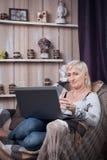 Séance femelle supérieure dans la chambre et l'Internet confortables de lecture rapide avec de la La Image stock