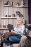 Séance femelle supérieure dans la chambre et l'Internet confortables de lecture rapide avec merci Photographie stock