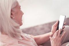 Séance futée satisfaisante de femme et à l'aide de son smartphone Photo stock
