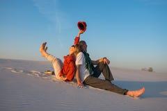 Séance heureuse de couples, de nouveau au dos, dans le désert contre un bleu Photos stock