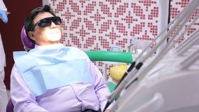 Séance masculine asiatique dans la chaise dentaire avec des verres de l'ultraviolet