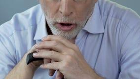 Séance masculine supérieure avec des mains sur le bâton de marche commençant à tousser, problèmes de poumon banque de vidéos