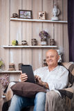 Séance masculine supérieure dans la chambre et l'Internet confortables de lecture rapide avec le tabl Photographie stock libre de droits