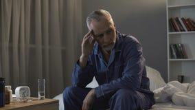 Séance masculine supérieure dans le lit et douleur de mal de tête terrible la nuit photographie stock