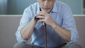 Séance masculine triste sur le divan avec le bâton de marche à disposition et penser à la vie Photos stock