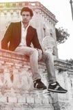 Séance modèle de jeune homme élégant sur le vieux mur du bas historique Beaux vieux hublots à Rome (Italie) image libre de droits