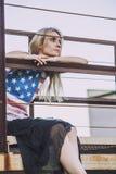 Séance modèle femelle à une balustrade dans un T-shirt avec l'Américain Images stock