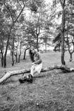 Séance modèle sexy sur le rondin en bois et regarder l'appareil-photo avec le regard de couvée photos libres de droits