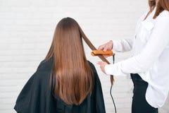 Séance modèle tandis que hairstyling dans le salon beaty avec les murs de briques blancs photo stock