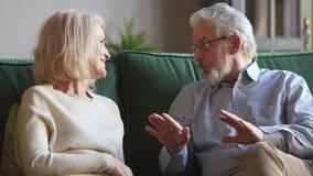 Séance parlante de vieux couples supérieurs de conjoints sur le sofa à la maison banque de vidéos