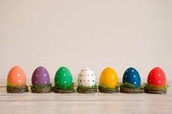 Séance peinte à la main d'oeufs de pâques dans les nids sur le fond blanc Joyeuses Pâques photographie stock libre de droits