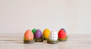 Séance peinte à la main d'oeufs de pâques dans les nids sur le fond blanc Joyeuses Pâques photos libres de droits