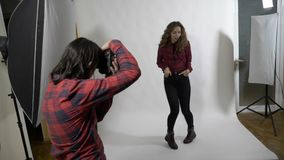 Séance photo de mouvement lent d'une célébrité dans un studio blanc professionnel de fond pour une couverture de magazine de femm banque de vidéos