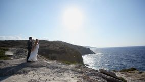 Séance photo romantique des jeunes mariés sur la plage leur jour du mariage banque de vidéos