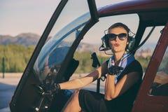 Séance pilote de femme attirante dans l'hélicoptère images libres de droits