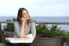 Séance songeuse de femme dans une terrasse d'un restaurant Photos stock