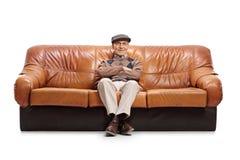 Séance supérieure sur un sofa en cuir Image stock