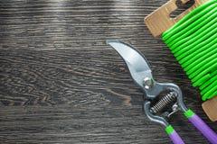 Sécateurs de fil de lien de jardin sur le conseil en bois Image stock