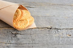 Séchez les biscuits salés dans un papier d'emballage sur un fond en bois de vintage avec l'espace de copie pour le texte Casse-cr Images stock