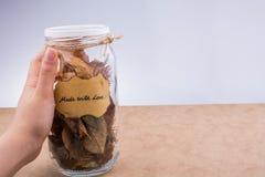 Séchez les feuilles dans des bouteilles sur le fond brun Photos stock