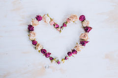 Séchez les fleurs roses dans la forme de coeur sur le vieux fond en bois Photographie stock