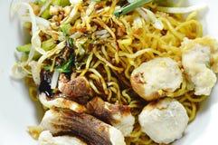Séchez les nouilles chinoises d'oeufs complétant le porc et la boule de tranche préparant la sauce de soja noire douce sur la cuv images stock